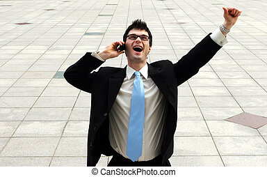 Businessman shows emotion as he gets great news on the telephone