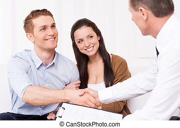Sealing a deal. Happy young man shaking hand to financial...