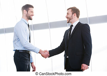 Sealing a deal. Two cheerful business men shaking hands and smiling while standing indoors