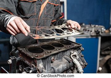Sealing gasket in hand. The mechanic disassemble block...