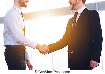 Sealing good deal. Two cheerful business men shaking hands and smiling while standing indoors