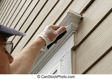 Sealing Window Leaks - Man outdoors filling holes that...