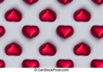 seamless tile of red shiny hearts in the snow, valentine background pattern