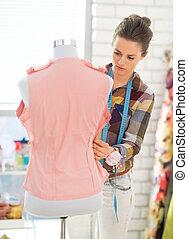 Seamstress adjusting clothing on mannequin