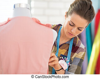 Seamstress adjusting clothing on mannequin