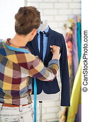 Seamstress adjusting suit on mannequin. rear view