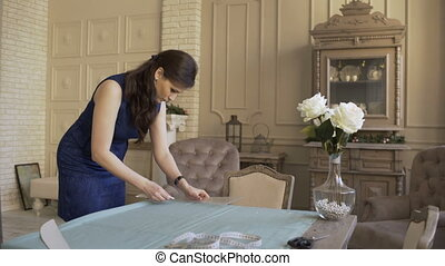 Seamstress and fashion designer at work. Young woman draw chock on the cloth in tailor studio