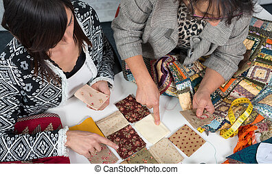 seamstress and her apprentice choose fabric for patchwork