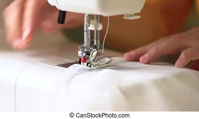 Seamstress at work. Sews the edges of the curtains with a straight line. White mesh fabric. Close up view.