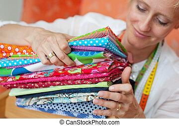 Seamstress choosing a fabric - Smiling young seamstress...