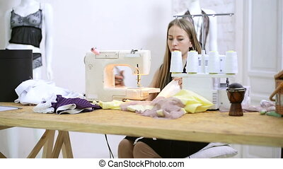 Seamstress cuts thread from lace fabric on sewing machines in atelier
