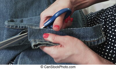 Seamstress hands cutting with scissors and Folding up the bottom of the Jeans