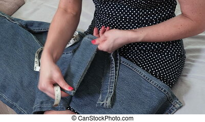 Seamstress hands Folding up the bottom of the Jeans