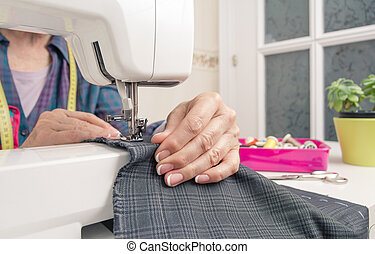 Seamstress hands working on a sewing machine