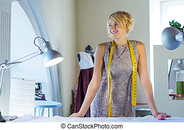 Young attractive needlewoman in studio standing at workplace