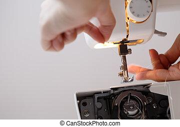 Seamstress inserts thread in sewing-machine