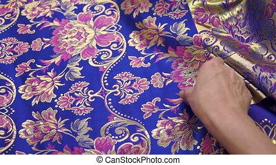 Seamstress Inspecting Fabric