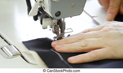 Seamstress machine-sewing a navy blue jacket. - Closeup of...