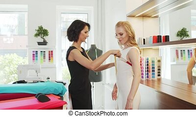 Professional seamstress measures the body of a client in a tailor shop.