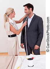 Seamstress measuring a man for a suit - Stylish blonde...