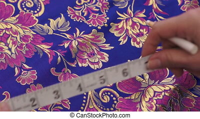 A seamstress measures and marks a beautiful colored fabric with her measuring tape and marking instrument.
