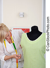 Seamstress measuring up a garment