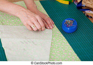 Seamstress pinning out a pattern