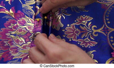 Closeup shot of a seamstress pleating fabric and putting pins into it to hold the material in place.