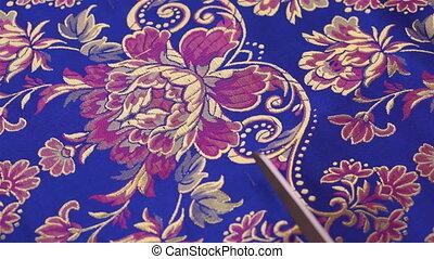 Seamstress Scissors Cutting Fabric - A seamstress cuts a...