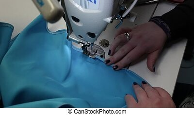 Close up high angle view of the hands of a seamstress sewing a fashion garment in blue fabric on a modern electric sewing machine