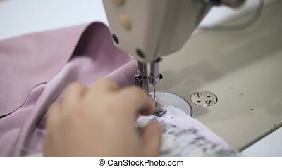 Seamstress sewing a pink bathrobe and taking out pins in the process