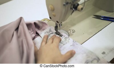 Seamstress sewing a pink bathrobe