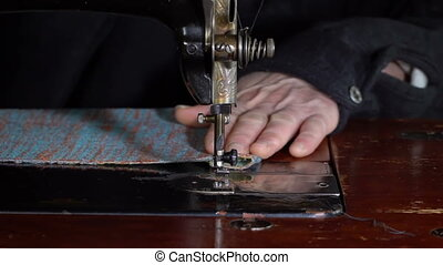Seamstress sews on a sewing machine. Slow motion