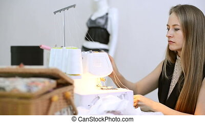 Seamstress sits and white thread inserts into the overlock....