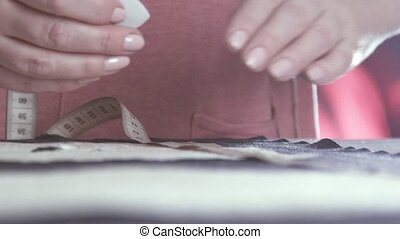 Seamstress tape measure applies to the fabric, and is pursuing a line
