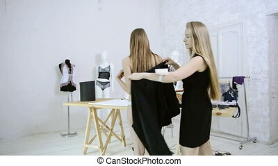 Seamstress tries on model of nightgown inside atelier