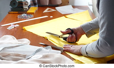 Seamstress with scissors cutting fabric. - Seamstress with...