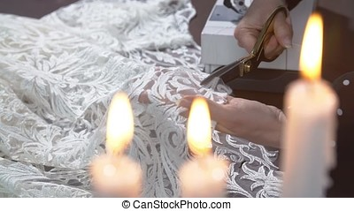Seamstress with tailor scissors cutting out fabric at studio
