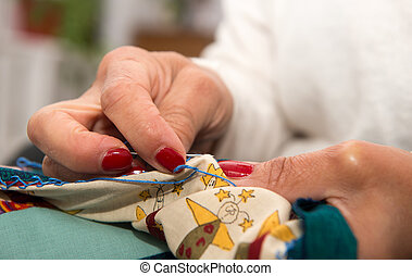 woman hands sewing for finish a quilt.