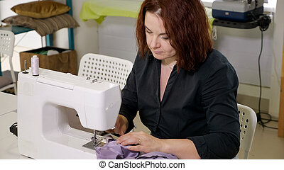 Seamstress woman is working on sewing machine in tailoring workshop business.