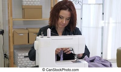 Seamstress woman is working on sewing machine in tailoring ...
