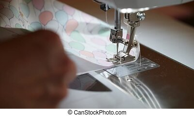 Seamstress working at sewing machine with textile