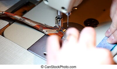 Seamstress in the working process, close-up sewing machine, factory, industry