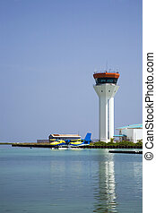 Seaplane and control tower - A sea plane lands on the water...