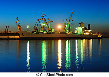 View on seaport with cranes and cargo ship at the night