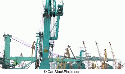 Seaport crane motion. Blue transportation crane. White sky...