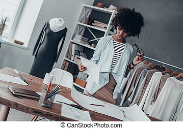 Searching for fashion muse. Serious young African woman holding eyeglasses and looking at paper while standing in her studio