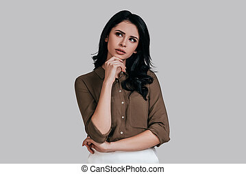 Searching for inspiration. Thoughtful young woman in smart casual wear holding hand on chin and looking away while standing against grey background