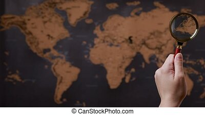 Hand with a magnifying glass guides the world map, Vacation search or geography study concept. High quality 4k footage
