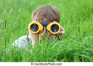 Searching - Young boy in a meadow looking through binoculars...